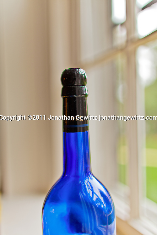 An empty blue wine bottle next to a window. WATERMARKS WILL NOT APPEAR ON PRINTS OR LICENSED IMAGES.