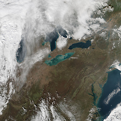 """November can be a stormy month in the Great Lakes region, as it was again in 2015. Toward the middle of the month, a low-pressure system and cold front swept up from the Central Plains and across the lakes. In Detroit, media outlets reported wind gusts as high as 52 miles (84 kilometers) per hour that left 13,000 residents without power. On Lake Erie, gale force winds halted shipping.<br /> Winds were not the only reason ships sought safe anchorage. The high winds created a seiche - a large standing wave that occurs when strong winds and a quick change in atmospheric pressure push water from one end of a body of water to the other, according to NOAA. Seiches occur periodically on Lake Erie. In 1844, a 22-foot seiche breached a sea wall with deadly consequences. In 2008, Buffalo was flooded by waves that measured 16 feet. That's about the height of the seiche measured by a buoy at the lake's east side on November 12, 2015.<br /> Two weeks after the seiche, its effects were still evident. On November 25, 2015, the Visible Infrared Imaging Radiometer Suite (VIIRS) on the Suomi NPP satellite acquired this natural-color image of colorful green and tan swirls.<br /> """"The seiche stirred up a lot of sediment,"""" said Kevin Czajkowski, a remote-sensing scientist at the University of Toledo. Not all of the colorful swirls are necessarily the result of resuspended sediments. """"I wonder if Lake Erie is having a whiting event as well.""""<br /> Particles of calcium carbonate in the water can cause lightening, or """"whiting,"""" of the water. That usually happens in response to changes in the water temperature, or due to increased photosynthesis by phytoplankton and other microscopic marine life.<br /> But Thomas Bridgeman, an environmental scientist at the University of Toledo, agrees that the swirls of color are mostly due to sediments. """"Little patterns along the shoreline suggest wind-driven sediment resuspension,"""" he said. """"There is an olive-green tint to part of the image that might be"""