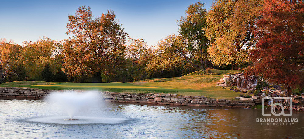 A beautiful colorful Autumn landscape with a flowing fountain in the water.