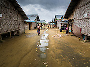 07 NOVEMBER 2014 - SITTWE, RAKHINE, MYANMAR: A Rohingya Muslim woman walks through the IDP camp she lives in. The camp doesn't have sewage and water runs through the dirt street after a rain. After sectarian violence devastated Rohingya communities and left hundreds of Rohingya dead in 2012, the government of Myanmar forced more than 140,000 Rohingya Muslims who used to live in and around Sittwe, Myanmar, into squalid Internal Displaced Persons camps. The government says the Rohingya are not Burmese citizens, that they are illegal immigrants from Bangladesh. The Bangladesh government says the Rohingya are Burmese and the Rohingya insist that they have lived in Burma for generations. The camps are about 20 minutes from Sittwe but the Rohingya who live in the camps are not allowed to leave without government permission. They are not allowed to work outside the camps, they are not allowed to go to Sittwe to use the hospital, go to school or do business. The camps have no electricity. Water is delivered through community wells. There are small schools funded by NOGs in the camps and a few private clinics but medical care is costly and not reliable.   PHOTO BY JACK KURTZ