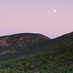 The moon rises over the notch between Dorr and Cadillac Mountains, Acadia National Park, Maine.