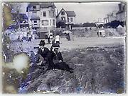 family posing on beach near hotel eroding glass plate early 1900s