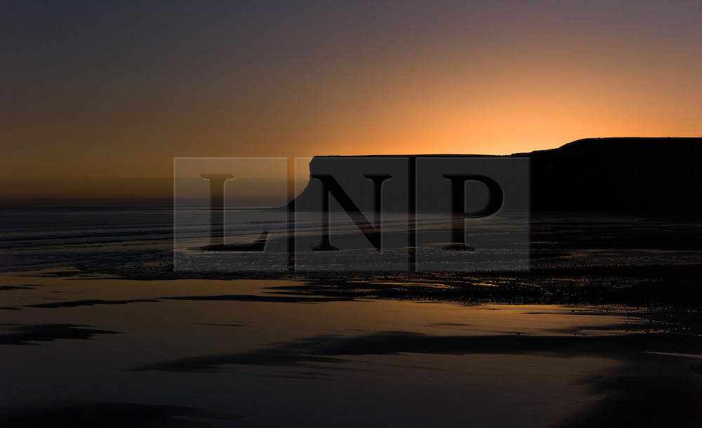 © Licensed to London News Pictures. 12/03/2014<br /> <br /> Saltburn, Cleveland, United Kingdom<br /> <br /> Huntcliff is silhouetted against the first light of dawn as it breaks over Saltburn in Cleveland.<br /> <br /> Photo credit : Ian Forsyth/LNP