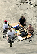 A group of men with their belongings placed on a floating door are being evacuated from a flooded area in New Orleans August 30, 2005. Hurricane Katrina strengthened into a rare top-ranked storm and barrelled into the vulnerable U.S. Gulf Coast for a second and more deadly assault on the Gulf Coast. REUTERS/Rick Wilking
