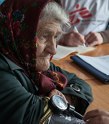 Dr Moshin Mehraj checks the pulse of an elderly patient at the MSF mobile clinic in the village of Gorodishe, near Lugansk.