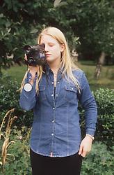 Teenage girl standing outdoors using video camera,