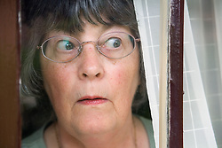 Woman; looking surprised; staring through curtains,