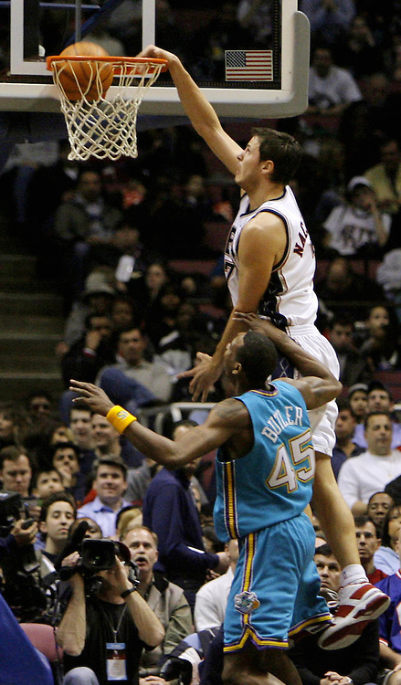 The Nets' Bostian Nachbar dunks over the Hornets' Rasual Butler during the first half of the game between the New Orleans/Oklahoma City Hornets and the New Jersey Nets at Continental Airlines Arena in East Rutherford, New Jersey on Wednesday 21 February 2007.