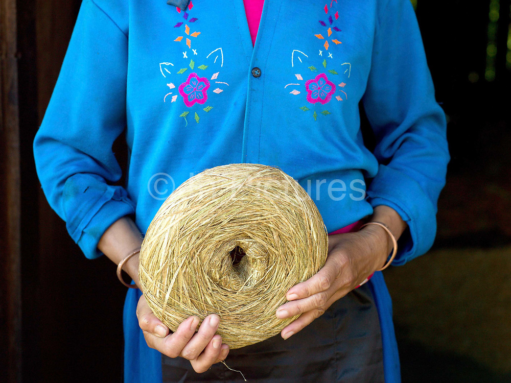 Mee, a Hmong Lai woman holds a roll of spliced hemp in Ban Tatong, Phongsaly province, Lao PDR. Making hemp fabric is a long and laborious process; the end result is a strong durable cloth with qualities similar to linen which the Hmong women use to make their traditional clothing. In Lao PDR, hemp is now only cultivated in remote mountainous areas of the north. The remote and roadless village of Ban Tatong is situated along the Nam Kang river (an offshoot of the Nam Ou) and will be relocated due to the construction of the Nam Ou Cascade Hydropower Project Dam 7.