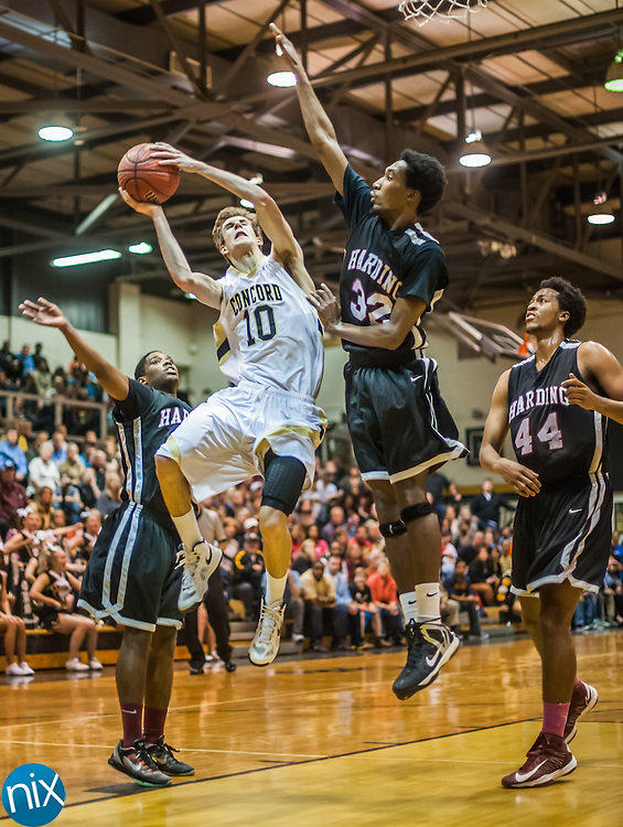 Concord's Connor Burchfield goes up for a shot against Harding's Emmanuel Patton during the third round of the NCHSAA 3A playoffs Friday night at Concord High School. Harding defeated the Spiders 71-65.
