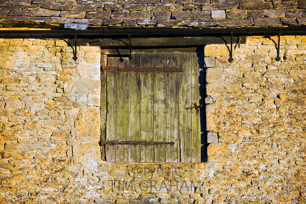 Old wooden door on a stone barn in the Cotswolds, Gloucestershire
