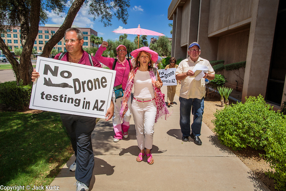 """31 JULY 2012 - PHOENIX, AZ:  MEDEA BENJAMIN, center, and other members of Code Pink march around the Arizona State Capitol Tuesday. Medea is a political activist, best known for co-founding Code Pink and, along with her husband, activist and author Kevin Danaher, the fair trade advocacy group Global Exchange. She was also a Green Party candidate in 2000 for the United States Senate. She appeared in Phoenix to promote her new book, """"Drone Warfare: Killing by Remote Control."""" She, and other members of Code Pink, presented a letter to Arizona Gov. Jan Brewer protesting Brewer's request to use the state's airspace to train drone pilots.  PHOTO BY JACK KURTZ"""