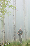 Obadiah Reid hikes through an aspen grove in fog along the Hankins Pass Trail, Lost Creek Wilderness, Colorado.