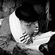 An old man reads sacred scriptures in the Tunnel of the Asmoneos, located next to the Wall of the Lamentations. Jerusalem.Israel