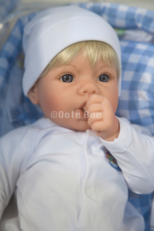 face of a blond caucasian baby doll with thumb in the mouth