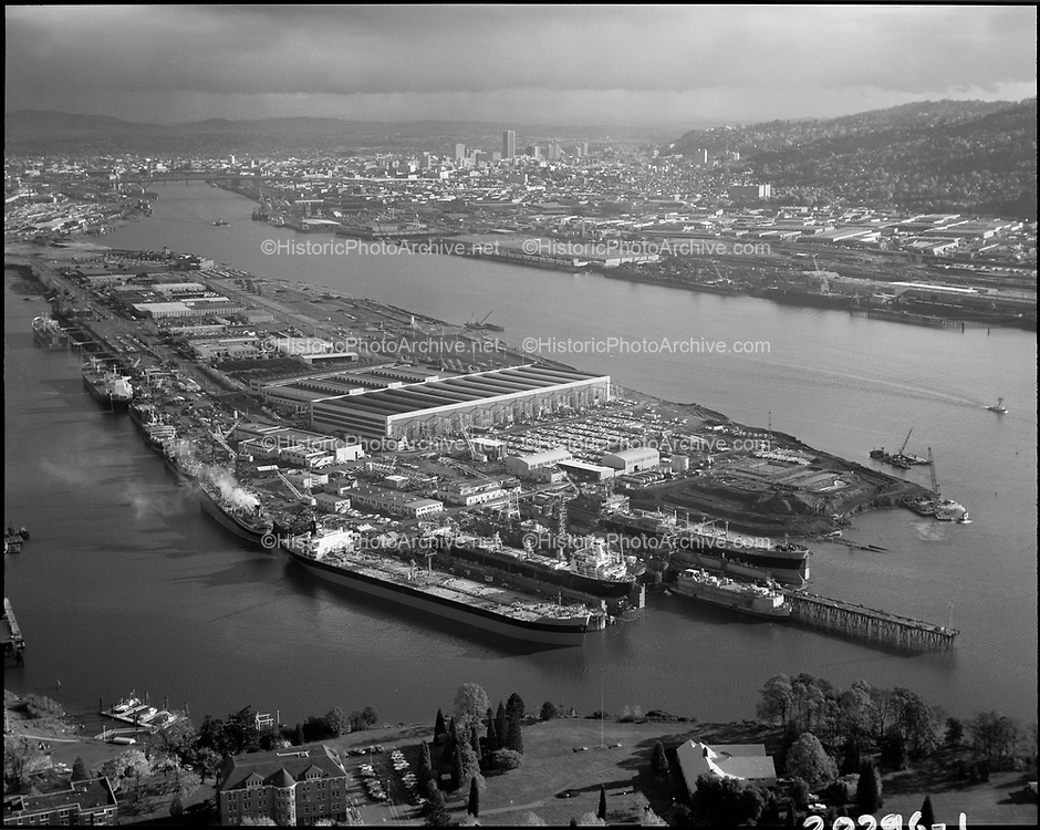 """Ackroyd 20296-1. """"Port of Portland. aerials. Swan Island. November 11, 1977"""" (Caption published in Daily Journal of Commerce, November 11, 1977, pg. 1: """"Full house at Swan Island drydocks. Port of Portland's Swan Island drydock and ship repair area reflect an increase in activity this fall, compared to last year. The three drydock (foreground) bays are occupied as ar four repair berths o the left side. Earth-moving activity next to the drydock is for the fourth drydock in spring, 1978. In background is the skyline of downtown Portland."""""""