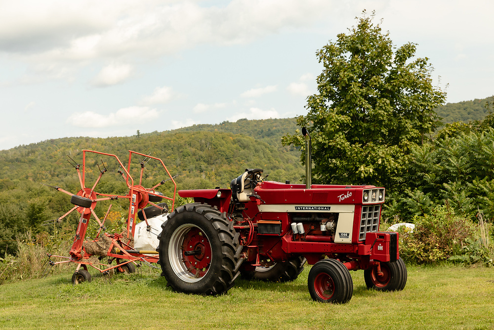 An old International Harvester tractor with a tedder attached sitting on a hilltop farm in Vermont.