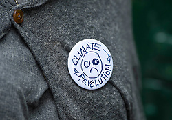 """© London News Pictures. 16/08/2013. Balcombe, UK. A """"CLIMATE REVOLUTION"""" badge worn by Designer Vivienne Westwood arriving at Balcombe train station to join Campaigners demonstrating outside the Cuadrilla drilling site in Balcombe, West Sussex which has been earmarked for fracking. Cuadrilla has temporarily ceased drilling at the site under advice from the police after campaign group No Dash For Gas threatened a weekend of civil disobedience. Photo credit: Ben Cawthra/LNP"""