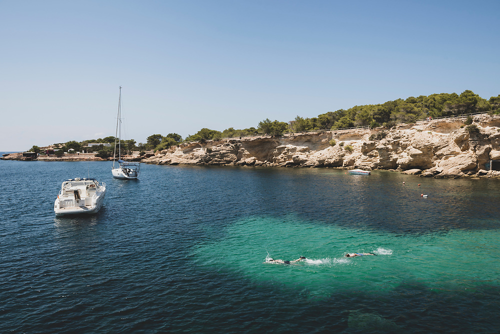 People swim in a small cove on the Mediterranean Sea near San Antonio, Ibiza. A sailboat and speedboat are anchored in the bay. (July 30, 2018)