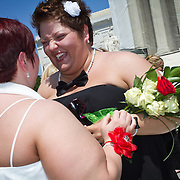 Shannon Glatz, left, and Liberty Manos, of Akron, Ohio, celebrate after exchanging vows near the steps of the Supreme Court of the United States, on June 21, 2013.  Twenty-five gay couples traveled to Washington on the C-Bus of Love to get married en masse the week before decisions are expected to be made on the Defense of Marriage Act (DOMA) and Proposition 8. John Boal photography