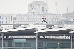 A stunt double runs along Blackfriars Bridge in London, during filming for Mission Impossible 6.