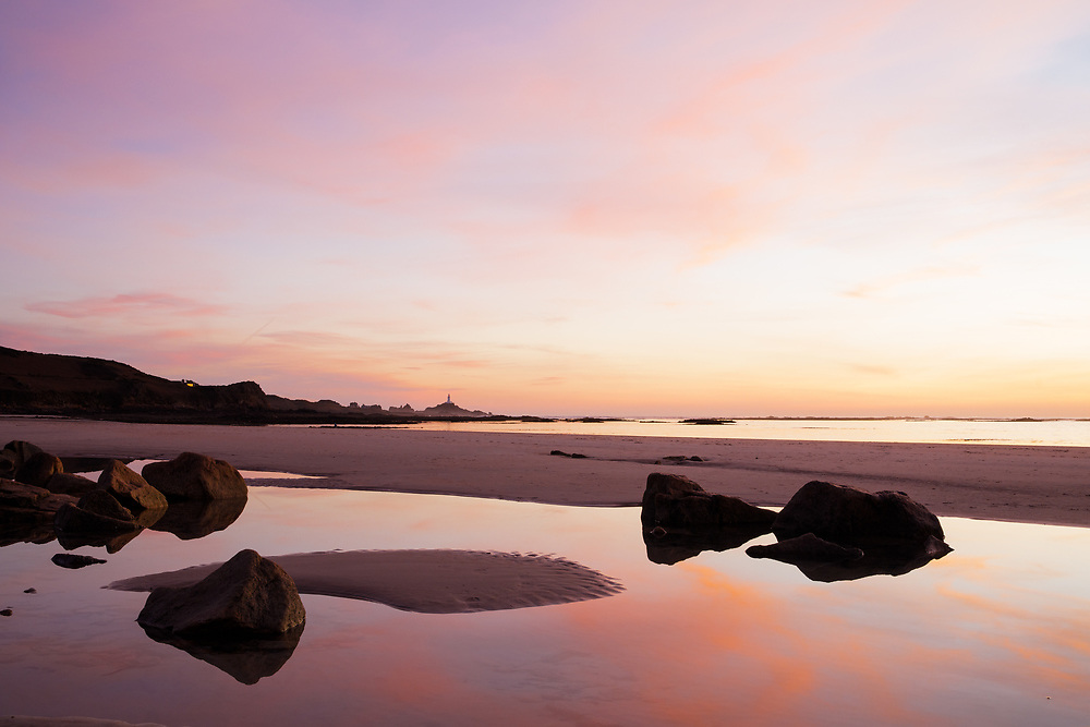Pink sky reflecting in the glassy calm water in the rock pools at St Ouen's Bay, Jersey at sunset, with views of Corbiere Lighthouse in the distance