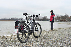 Man standing with pedelec at the lakeshore during winter, Bavaria, Germany