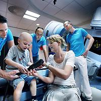 Nederland, Amsterdam , 25 mei 2012..Frederieke Vriends, Hoofd Paramedische Sectie samen met patientje en medewerkers van de afdeling Radiotherapie bij een bestralingsapparaat..Het patientje hoiudt de afstandbediening van het bestralingsapparaat vast..Foto:Jean-Pierre Jans