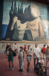 Tourists including young boy with disability; who is wheelchair user; visiting the Dali Museum in Figueres; with large painting on the wall behind them,