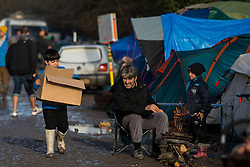 © Licensed to London News Pictures. 23/01/2016. Dunkirk, France. A boy carrying a cardboard box through the Dunkirk migrants camp on the day that Leader of the Labour Party JEREMY CORBYN visited both the  'Jungle' in Calais and the Dunkirk camp where thousands of migrants and refugees attempting to reach the UK are currently living. Photo credit: Ben Cawthra/LNP