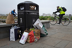 © Licensed to London News Pictures. 01/04/2021. London, UK. Members of the public cycle past an overflowing bin in Cutty Sark Gardens after large groups of people visited to enjoy the warm weather and take advantage of new lockdown rules that allow groups of six to meet outside. Photo credit: George Cracknell Wright/LNP
