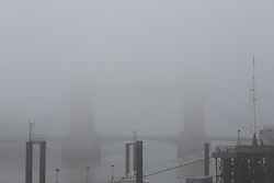 © Licensed to London News Pictures. 17/12/2016. LONDON, UK.  Tower Bridge is barely visible during foggy weather this morning. London and the River Thames was shrouded in thick fog this morning.  Photo credit: Vickie Flores/LNP