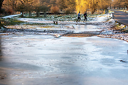 © Licensed to London News Pictures. 10/02/2021. London, UK. Runners run past a frozen cycle path in Richmond Park, South West London this morning. The Met Office have issued weather warnings for extreme cold with temperatures forecast to drop to as low as -10c in London tonight as Storm Darcy continues to bring travel chaos to the South East and the rest of the UK.  Photo credit: Alex Lentati/LNP