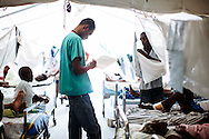 Dr. Gerald Dagrin looks at patients' charts at Choscal Hospital in Cite Soleil, Port-au-Prince, Haiti. The nongovernmental organization Medecins Sans Frontieres staffs physicians and nurses at the hospital.