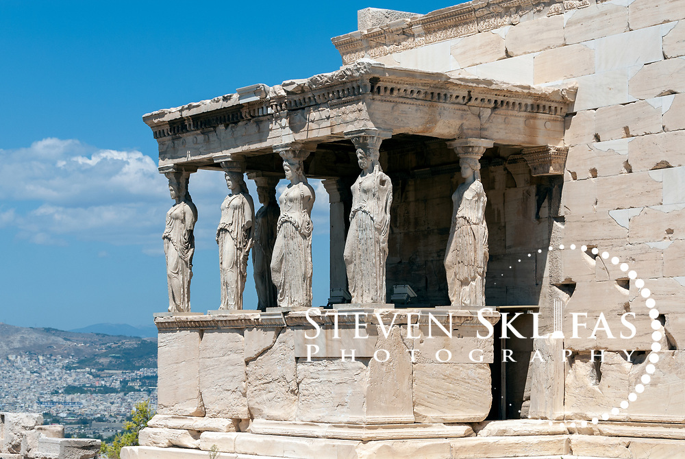 Acropolis. Athens. Greece. View of the famous Caryatid porch on the south side of the Erechtheion on the Acropolis summit. The porch or balcony has six sculptured graceful figures of maidens supporting the entablature. These figures are copies, five of the original six maidens are displayed in the new Acropolis museum and the sixth looted by Lord Elgin is on display in the British Museum. Built between 420 and 406 BC, the elegant and unusually shaped Erechtheion Temple was designed to incorporate a number of ancient sanctuaries and cults including that of Athena and her olive tree and Poseidon-Erechtheus. The Erechtheion was part of the monumental rebuilding and transformation of the Acropolis buildings during the time of Perikles. The Acropolis of Athens and its monuments are a UNESCO World Heritage Site.