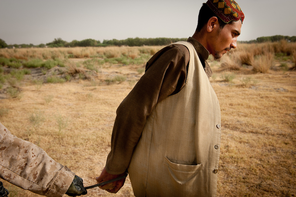 A Marine leads a detained Afghan insurgent back to Patrol Base Fires.