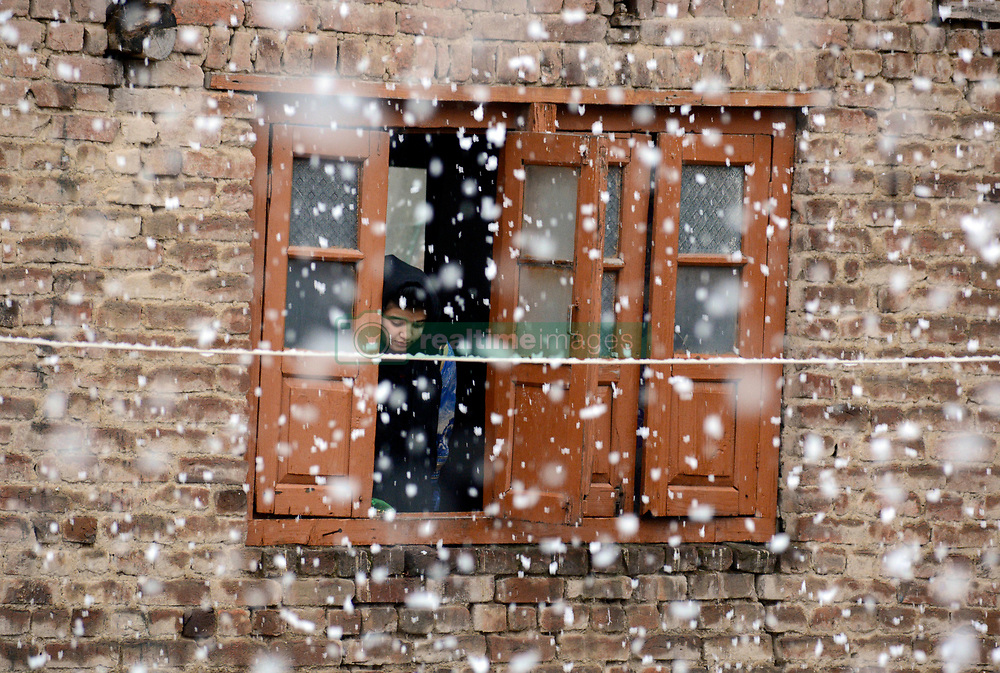 A Kashmiri young girl peeps through the window to enjoy the snowfall in Srinagar, the summer capital of Indian controlled Kashmir. Kashmir witnessed its first snowfall.