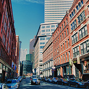View of South Street in the Leather District of downtown, Boston, MA. The Leather District is a small but growing sub-neighborhood of Chinatown. Located between Dewey Square and Kneeland Street, the Leather District is a nine-block area noted for its 19th century brick warehouse structures. These historic buildings were constructed primarily during the 1880s, with a design focused on efficient and economic manufacturing. The leather industry and related wholesalers required space for display, offices and work areas, thus, huge, ground floor display windows don these buildings, set in sturdy cast iron columns - a unique signature of the Leather District.
