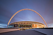 Wembley stadium in the warm glow of the setting sun. The home venue of the England national football team. Capacity 90.000 seats and including standing places 105.000. The Wembley arch which supports the roof is 134m high (440 ft).<br /> <br /> Architect: Fosters & Partners