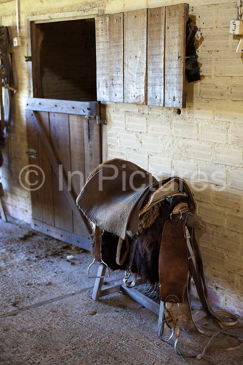 Saddle in front of stable door. Working Gaucho Fazenda in Rio Grande do Sul, Brazil.