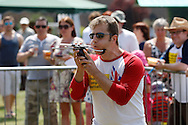 Photo by Andrew Tobin/Tobinators Ltd - 07710 761829 - 2012 world champion Rob Bresler takes aim with his balanced, chin supported, laser sighted peashooter during the World Peashooting Championships held at Witcham, Cambridgeshire, UK on 13th July 2013. Run in conjunction with the village fair, the Championships have been held in Witcham since 1971 when they were started by a Mr Tyson, the village schoolmaster, in order to raise funds for the village hall.Competitors come from as far afield as the USA and New Zealand to attempt to win the event. The latest technology is often used, including laser sights and titanium and carbon fibre peashooters. All peashooters must conform to strict length rules, not exceeding 12 inches, and have to hit a target 12 feet away. Shooting 5 peas at a plasticine target attached to a hay bale, the highest scorers move through the initial rounds to a knockout competition, followed by a sudden death 10-pea shootout.