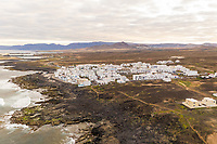 Aerial view of a coastal village in Canary island archipelago with traditional white houses, Tinajo, Spain.