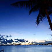 A beautiful blue glow in the sky in the Caribbean with a palm tree and sailing boat silhoetted sky just after the sun has set.