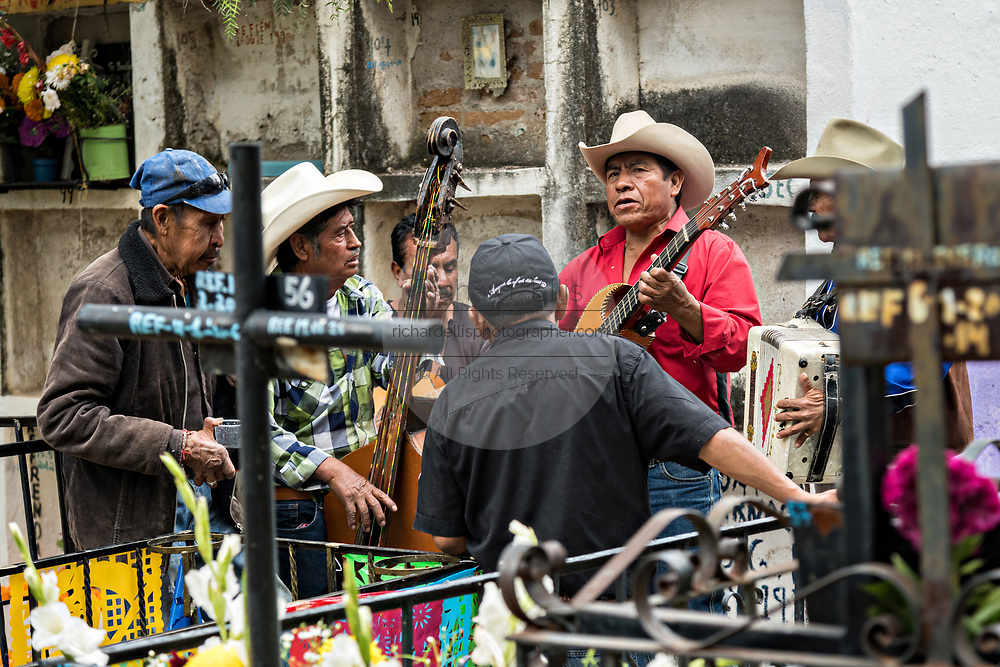 A Mexican Mariachi band plays at a decorated grave site in Our Lady of Guadalupe cemetery during the Dead of the Dead or Dia de Muertos festival in San Miguel de Allende, Mexico. The multi-day festival is to remember friends and family members who have died using calaveras, aztec marigolds, alfeniques, papel picado and the favorite foods and beverages of the departed.