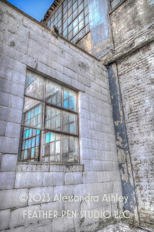 View through a broken window into an old Rust Belt factory building.