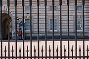 AQueens Guard seen through the iron railings at Buckingham Palace on the 29th August 2019 in London in the United Kingdom.
