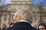 We see the famous blonde hair of London Mayor Boris Johnson as he is interviewed in Trafalgar Square. Alexander Boris de Pfeffel Johnson (born 19 June 1964) is a British politician and former journalist who has served as Mayor of London since 2008. He previously served as the Member of Parliament (MP) for Henley from 2001 until 2008. A member of the Conservative Party. As the sculpture known as Gift Horse, by German artist Hans Haacke, is unveiled in London's Trafalgar Square on the public space called the Fourth Plinth. Johnson financed the 10th artwork to appear here. The skeletal, riderless horse (derived from The Anatomy of a Horse - George Stubbs, 1766) with a London Stock Exchange tickertape is a comment on power, money and history.