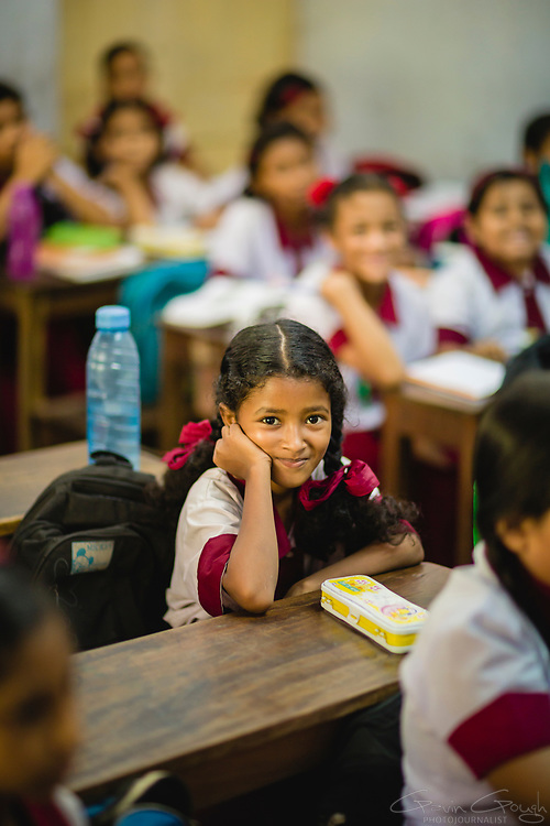 A smiling schoolgirl sitting at her desk in the classroom, Borisha High School, Bahela, Kolkata, India
