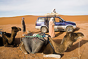 Two Berber men transfer supplies from the camels to a blue off road vehicle for the return trip from the sand dunes of Erg Zehar to the frontier town of M'hamid, Morocco, while a westerner watches.