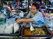 20 JUNE 2018 - BANGKOK, THAILAND: A food vender at Makkasan Market, a small local market in central Bangkok, prepares take away orders of rice in plastic bags. Officials in Thailand are wrestling with Thais use of plastic bags. The issue became a public one in early June when a whale in Thai waters died after ingesting 18 pounds of plastic. In a recent report, Ocean Conservancy claimed that Thailand, China, Indonesia, the Philippines, and Vietnam were responsible for as much as 60 percent of the plastic waste in the world's oceans.     PHOTO BY JACK KURTZ